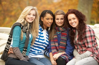 1239111-766964-group-of-four-teenage-girls-sitting-on-bench-in-autumn-park