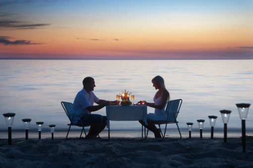 A-young-couple-share-a-romantic-dinner-with-candles-and-wine-glasses-on-the-sea-sand-beach