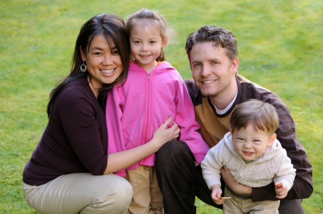 diverse family smiles / cuddling together outdoors / with grass in behind