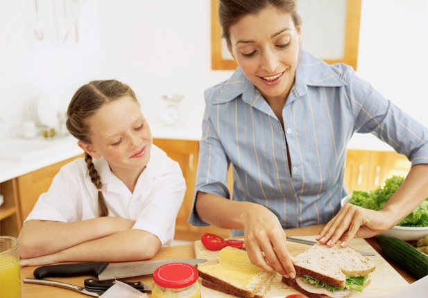 Young mother making a ham sandwich with a young girl (8-10) watching her