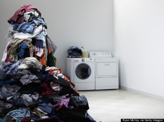Laundry room with tall pile of clothes.