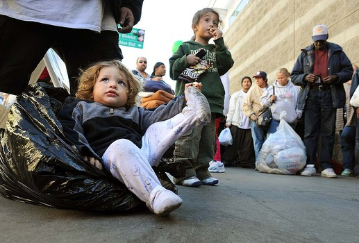 LOS ANGELES, CALIFORNIA NOVEMEBR 25, 2010-David Scala, 1, sits on a bag with the family belongings as his brother Mario, 4, watches a band during 67th Annual Traditional Banquet on Skir Row in Downtown Los Angeles Thursday. (Wally Skalij/Los Angeles Times)