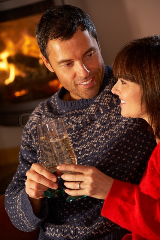 4316112-middle-aged-couple-sitting-sofa-by-cosy-log-fire-with-glass-of-champagne