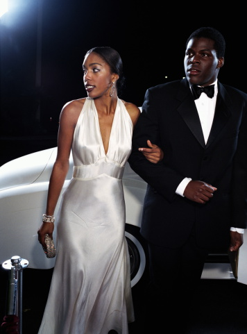 Young couple in formal attire, car in background