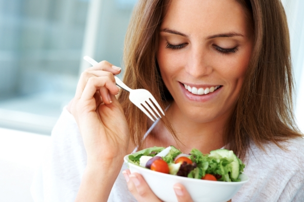 Closeup portrait of a happy young lady eating fruit salad