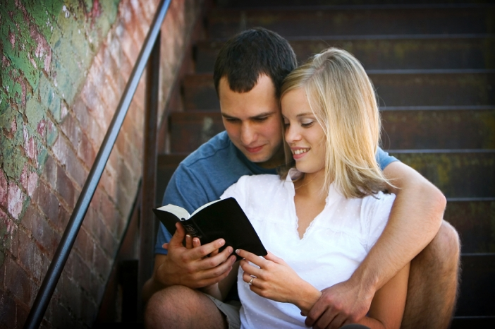 young-couple-reading-bible-on-stairs