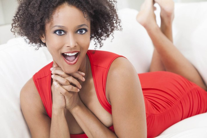 A-beautiful-mixed-race-African-American-girl-or-young-woman-laying-down-wearing-a-red-dress-looking-happy-and-surprised-