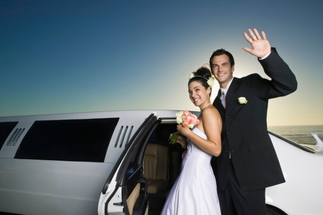 Newlyweds smiling by limousine
