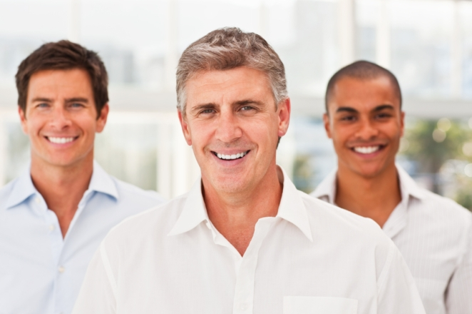 Portrait of a happy confident mature business man with his young male colleagues