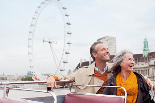 Happy couple riding double decker bus in London