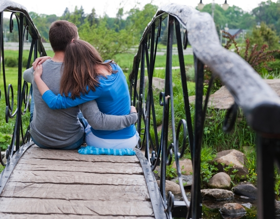 Happy couple is sitting and embracing on bridge