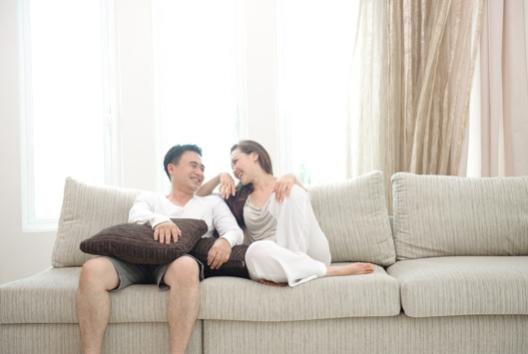 Happy asian couple sitting on the sofa enjoying each others company