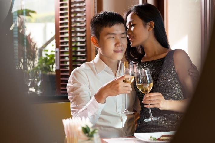 Beautiful woman whispering something sweet to her boyfriend