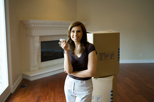 Woman in empty room with moving boxes, holding house key