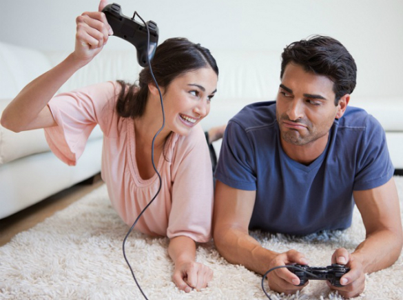 Woman beating her fiance while playing video games in their living room