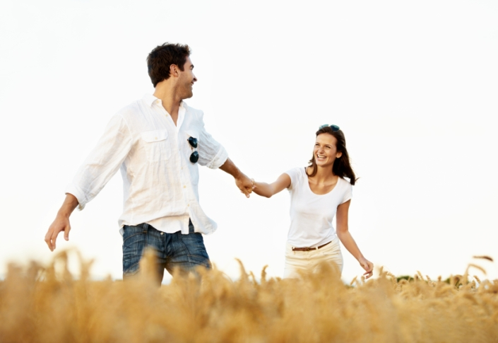 Handsome young guy leading his smiling girlfriend through a corn field