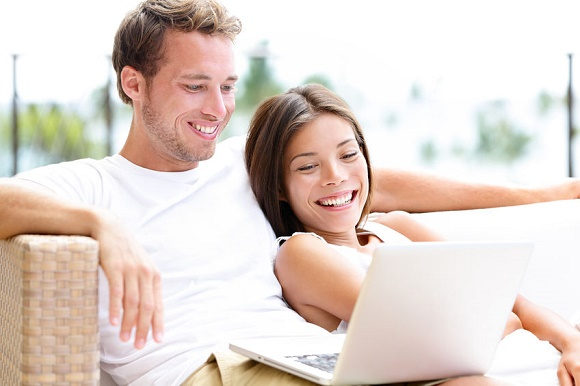22672811 - couple in sofa with laptop pc computer at home laughing happy relaxing together having fun. romantic young happy multiracial couple lying resting having fun together watching a movie. man and woman.