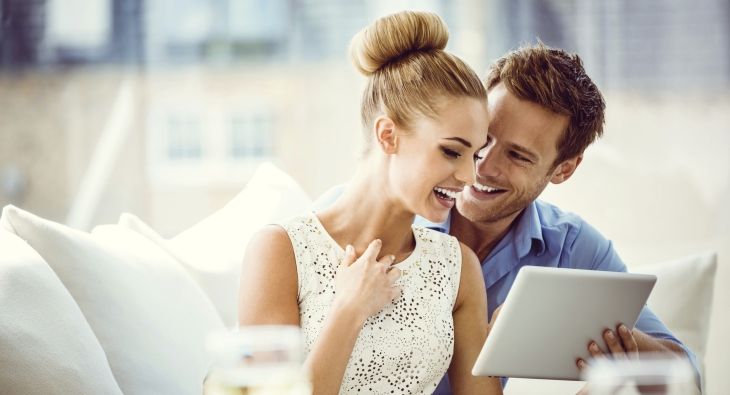portrait-of-happy-couple-sitting-on-sofa-at-home-and-using-a-digital-tablet-2