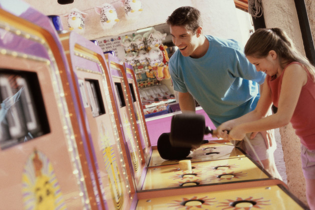 Daughter playing games with her father standing beside her in an amusement park