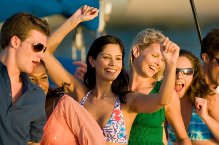 Group of young people enjoying a party on board a yacht at sunset.
