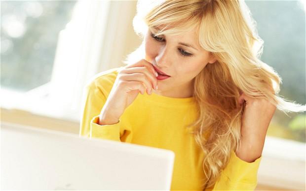 C8J73F Girl smiling using laptop
