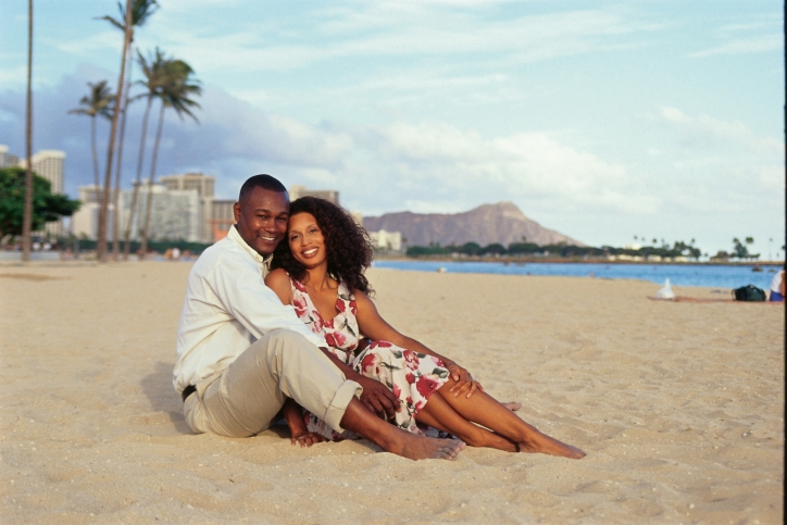 Young couple sitting in Waikiki Beach. Leahi, also known as Diamond Head background.