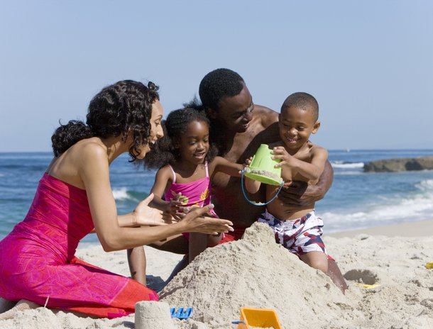 African American family making sand castle together on beach --- Image by © Ian Lishman/Juice Images/Corbis