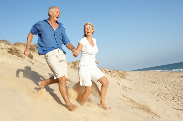Senior Couple Enjoying Beach Holiday Running Down Dune