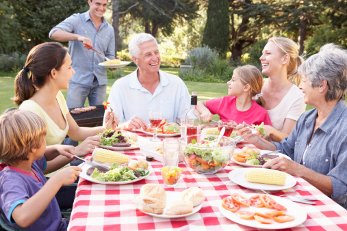 family-enjoying-barbeque-in-garden-together-summer