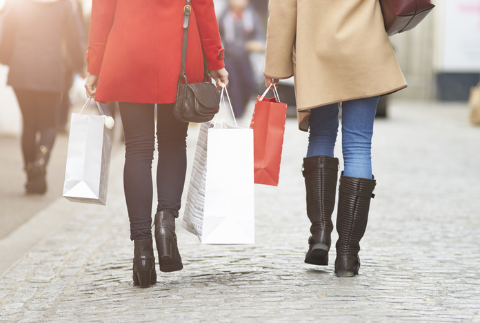 Woman walking along street with Christmas shopping