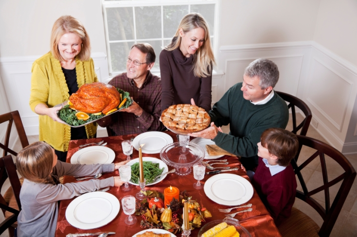 Multi-generation family enjoying traditional holiday meal, grandmother serving turkey and mother holding pie.