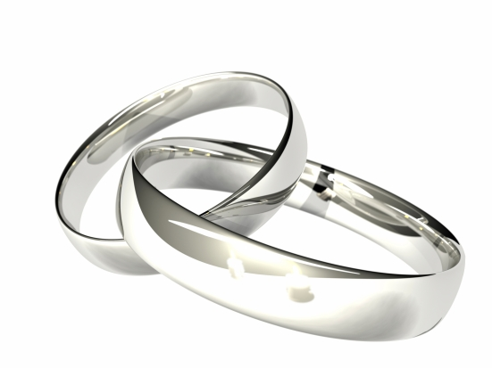 Computer rendered. Two linked rings in platinum or silver. Two candles reflected. Shallow depth of field.