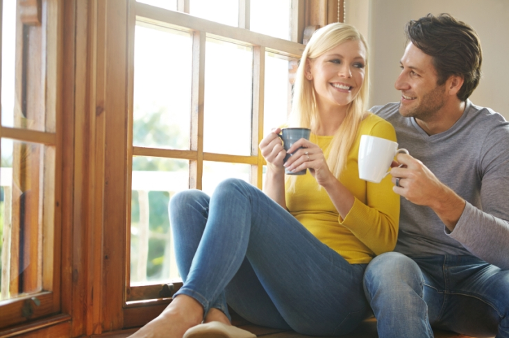 Shot of a happy couple enjoying a hot drink together next to a window at home